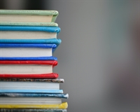 A pile of books on the left hand side with a grey background.