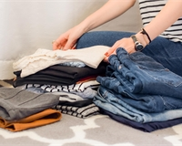 A person in a white and black striped t-shirt is sorting a pile of clothes