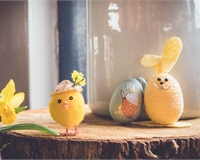 An Easter crafts scene, with a daffodil on left hand-side and handmade chick and bunny in center